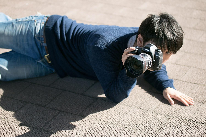 男が寝そべってカメラを構えている