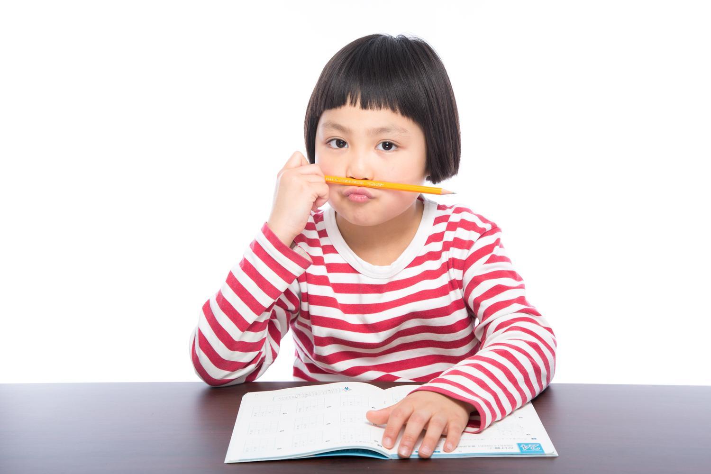 女の子が鉛筆を口と鼻の間に挟んでいる